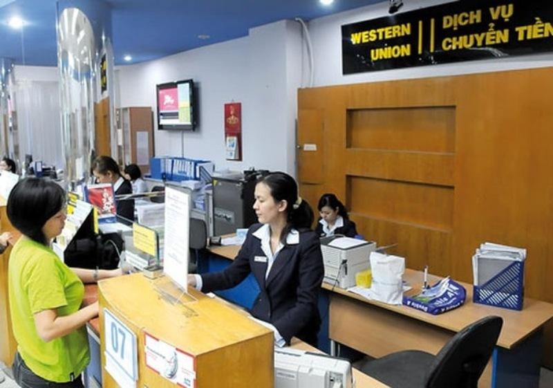 Nhân viên ngân hàng đưa phiếu nhận tiền cho khách hàng
